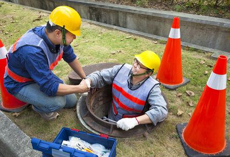 aguas residuales: dos trabajadores de alcantarillado en la boca de inspecci�n Foto de archivo