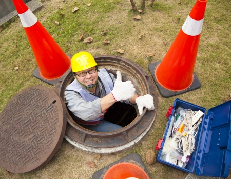 sewerage worker in the manhole with thumb up Stock Photo