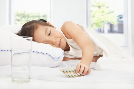 sick child holding medicine on the bed Stock Photo - 24477361