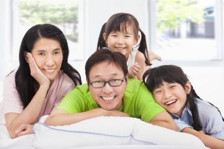 lifestyle: Familia asiática feliz en la cama