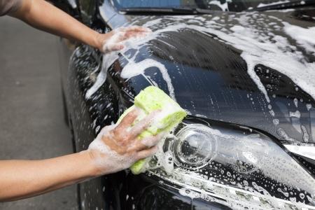 coche: manos sostienen esponja para lavar el coche