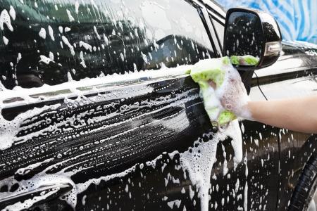 lavado: manos sostienen esponja para lavar el coche
