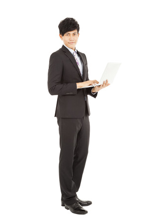 Full length of  young businessman standing with laptop Stock Photo - 24521143