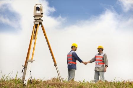 teodolito: dos ingenieros Surveyor apretón de manos en el campo Foto de archivo