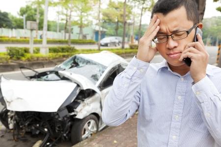 car crash: upset driver talking on mobile phone with crash car
