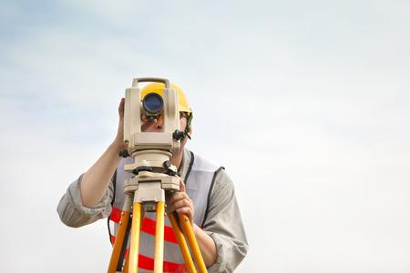 topografo: Ingeniero top�grafo haciendo medida con fondo de nubes Foto de archivo