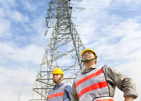 electricity generator: two workers standing before electrical power tower Stock Photo