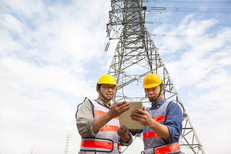 two workers standing before electrical power tower photo