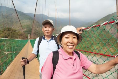 aventura: feliz asiático pareja de ancianos caminando sobre el puente en el parque natural