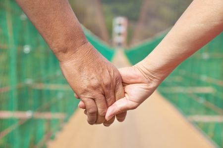 h�ndchen halten: �lterer Mann mit Frau Paar Hand in Hand zu Fu� auf der Br�cke Lizenzfreie Bilder