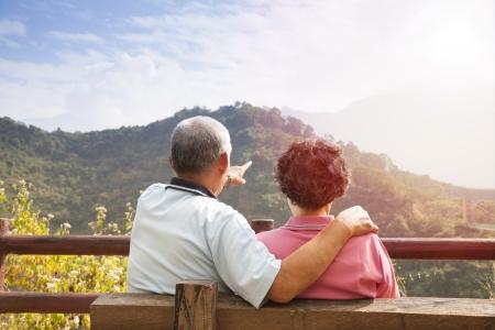 femme qui rit: couple de personnes �g�es assis sur le banc en regardant la vue de la nature