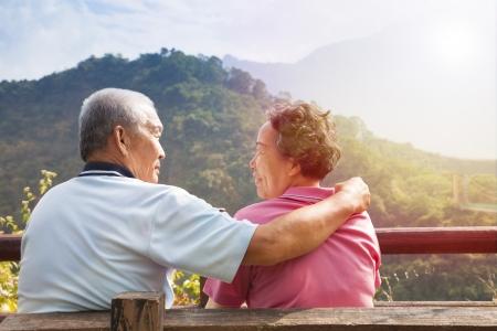 mujer descansando: pareja de ancianos sentados en el banquillo en el parque de la naturaleza Foto de archivo