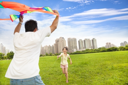 person outside: happy family playing colorful kite  in the city park