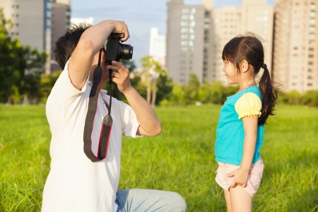 happy father taking picture with little girl in the city park photo