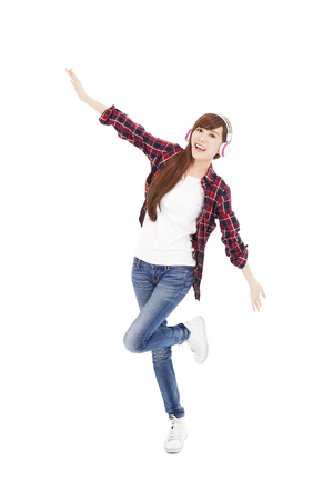 Young woman with headphones listening music and dancing photo