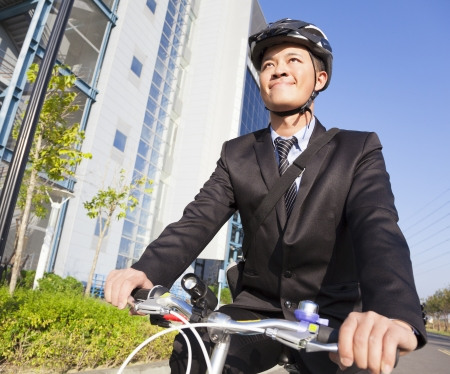 smiling businessman riding a bicycle to workplace photo