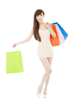 full length of smiling asian woman with shopping bags photo