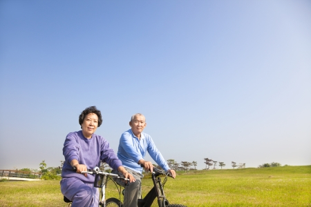pensioner: asian seniors couple biking in the park
