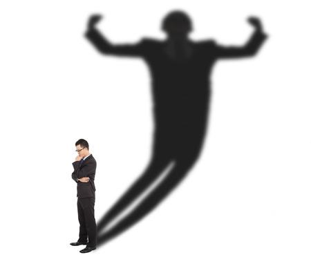 hombre fuerte: Hombre de negocios de pie y proyectando la sombra de un hombre fuerte Foto de archivo