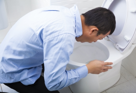 a toilet stool: Young man drunk or sick vomiting