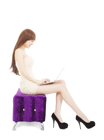 Fashionable young woman using laptop and sitting on sofa photo