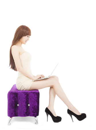 Fashionable  woman using laptop on sofa over white photo
