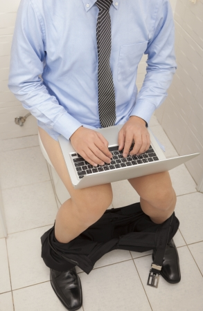 sitter: businessman using laptop working  in toilet  Stock Photo