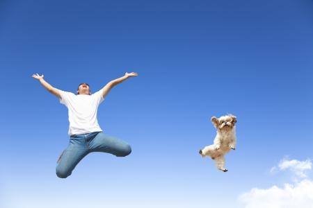 joven y perro que salta en el cielo