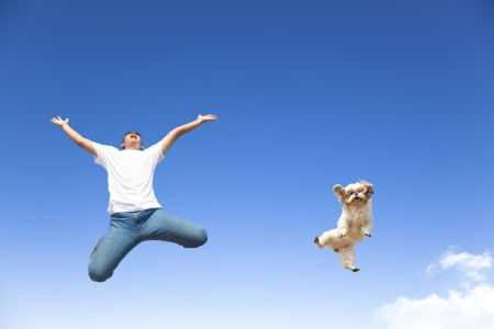 young man and dog jumping in the sky photo