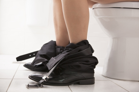 toilet roll: Close-up view of  business male sitting on the toilet seat Stock Photo