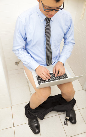 businessman  using time well working  in toilet with laptop . photo