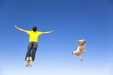 ontspannen jonge mens en hond springen in de lucht