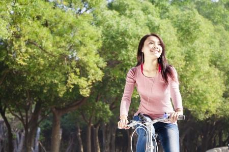 Hezká mladá žena na koni na kole v parku