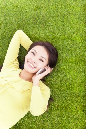 Woman smiling happily on a phone while lying grassland photo