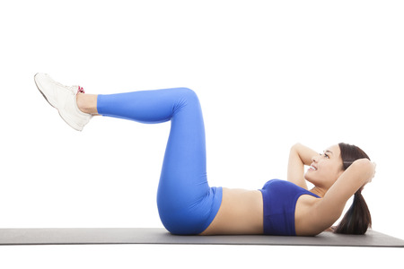 abdominal: Fit blonde doing pilates core exercise in studio