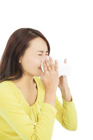 frio: mujer joven con un pañuelo y sonarse la nariz