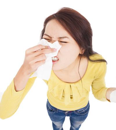 estornudo: Mujer joven que tiene alergia y soplando en el tejido Foto de archivo