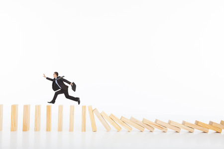 businessman running and catching  on toppling dominoes  photo