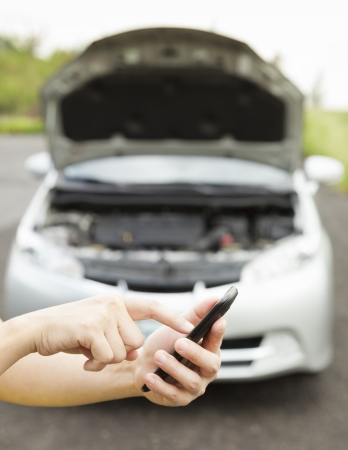 using cell phone to dial service number , a broken car Stock Photo