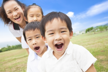 Asian smiling family playing on meadow and sunny day photo