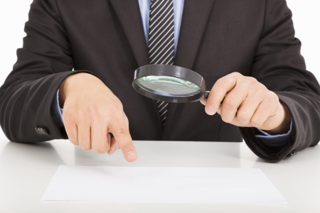 Businessman pointing through a magnifying glass to documents photo