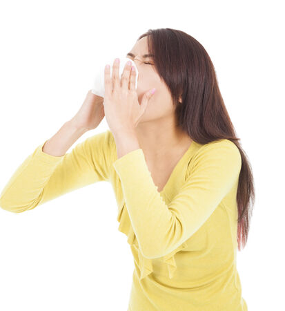 Young woman having flu or allergy and  blowing into tissue photo