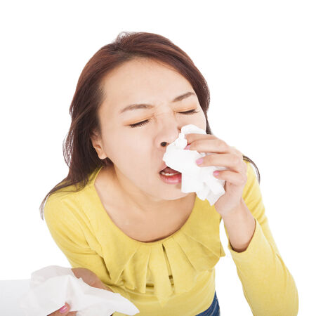 allergy: young woman with a an allergy sneezing into tissues Stock Photo