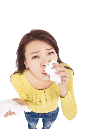 Sneezing and blowing nose,  young woman struggles with cold photo