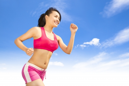 asian smiling runner woman jogging in sunny day photo