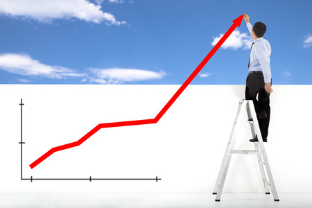 businessman standing on ladder drawing global diagrams Stock Photo - 25361711