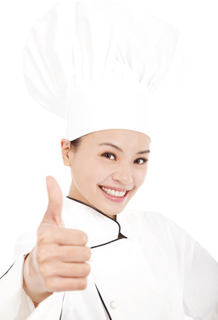 smiling female chef, cook or baker  showing thumbs up photo