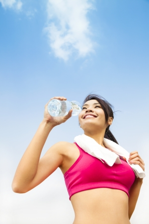 asian woman drinking water after fitness exercise photo