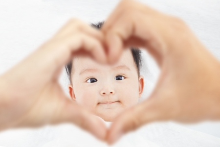 cute and smiling infant  with parents love hands  Standard-Bild
