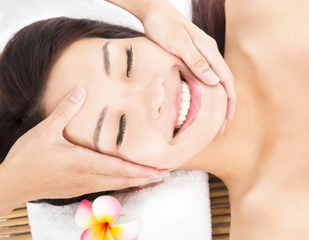 massage of face for asian woman in spa salon photo